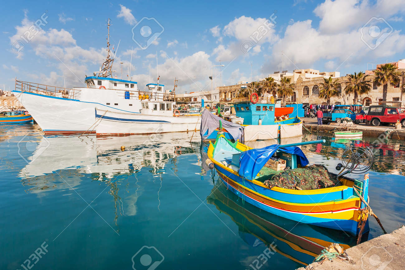 Mediterranean traditional colorful boats luzzu. Fisherman village in the south east of Malta. Early winter morning in Marsaxlokk, Malta. - 76425219