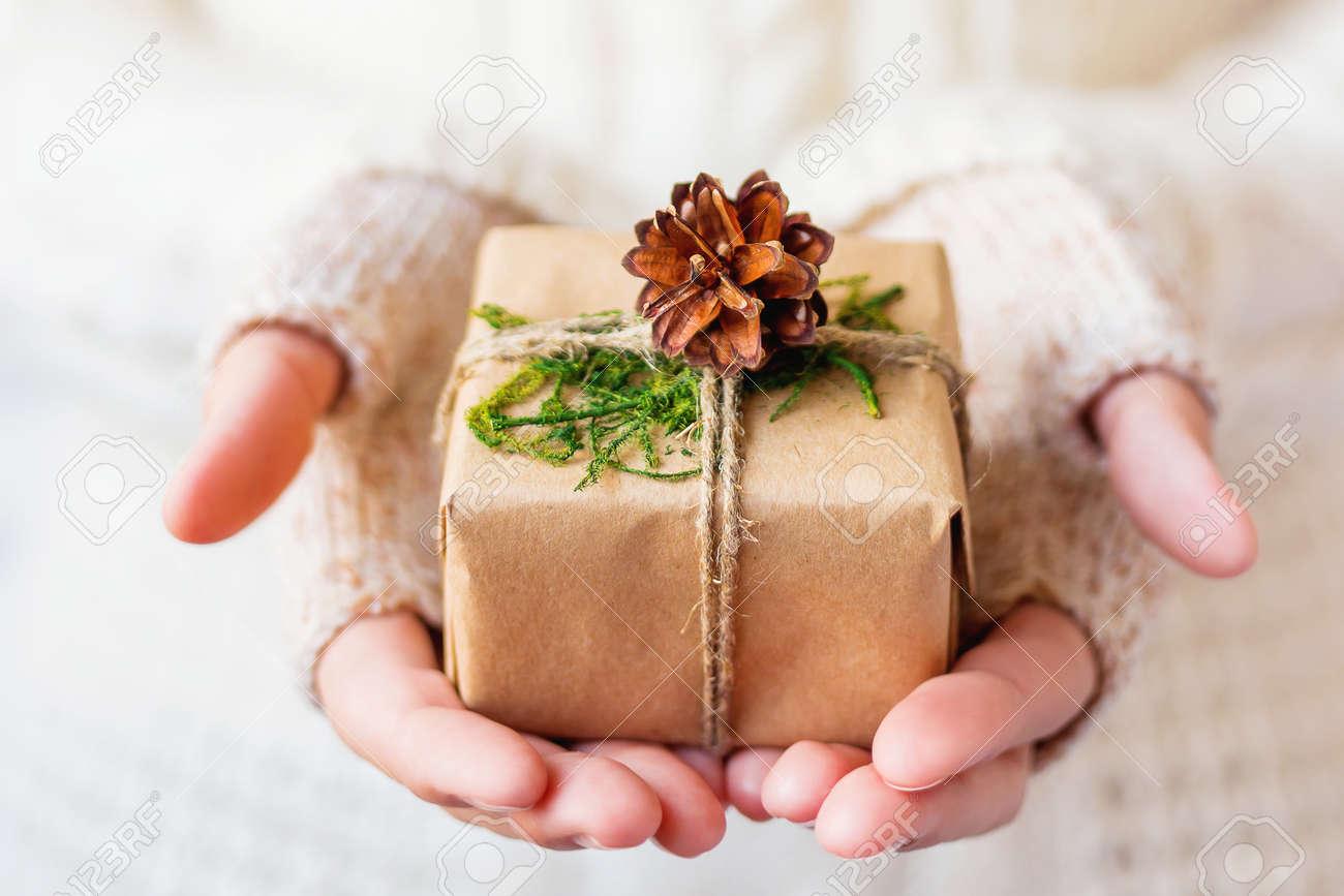 femme en pull tricoté tenant un cadeau. le cadeau est emballé dans