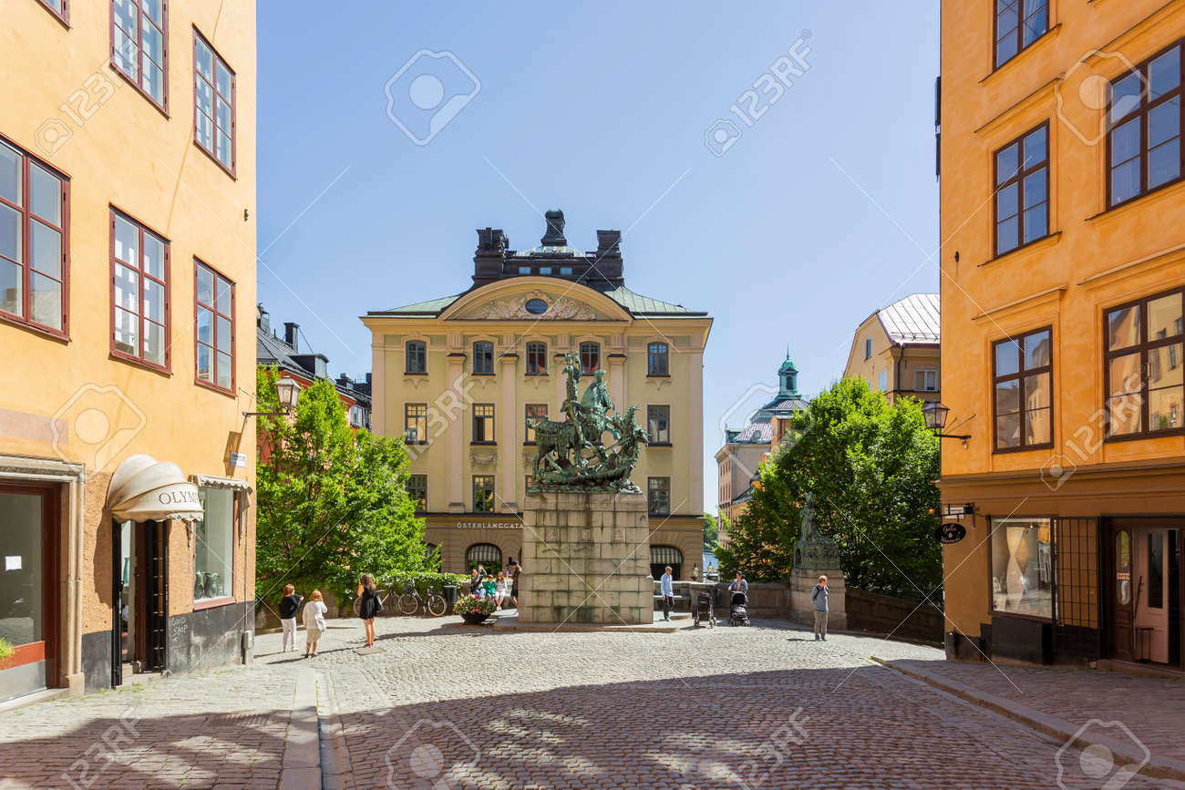 STOCKHOLM, SWEDEN - July 06, 2017. Tourists walk around bronze replica of Saint George and the Dragon sculpture by Bernt Notke. Antique buildings on Kopmantorget or Merchant's Square. - 171121785