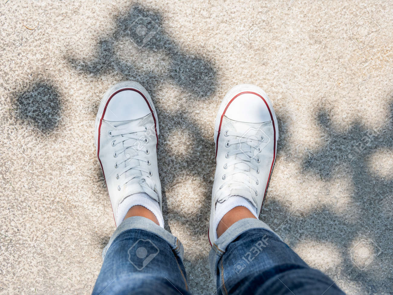 Woman feet in white sneakers on stone pavement. Top view on casual clothing and shoes at sunlight. Summer vibes. Modern urban fashion. - 172806619