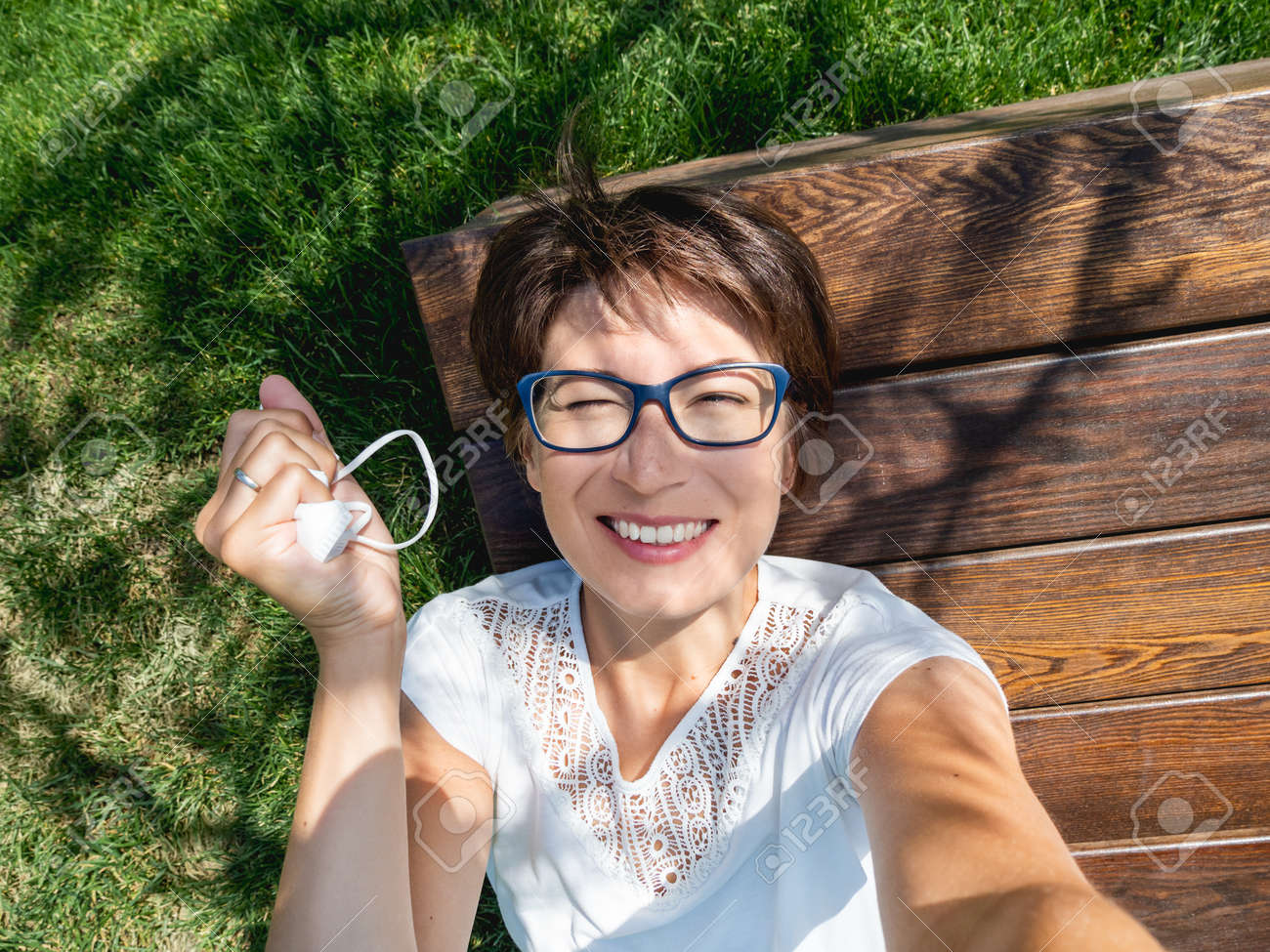 Smiling woman takes off medical protective mask to make selfie on her smartphone. Female in eyeglasses has a rest in urban park - 172806622