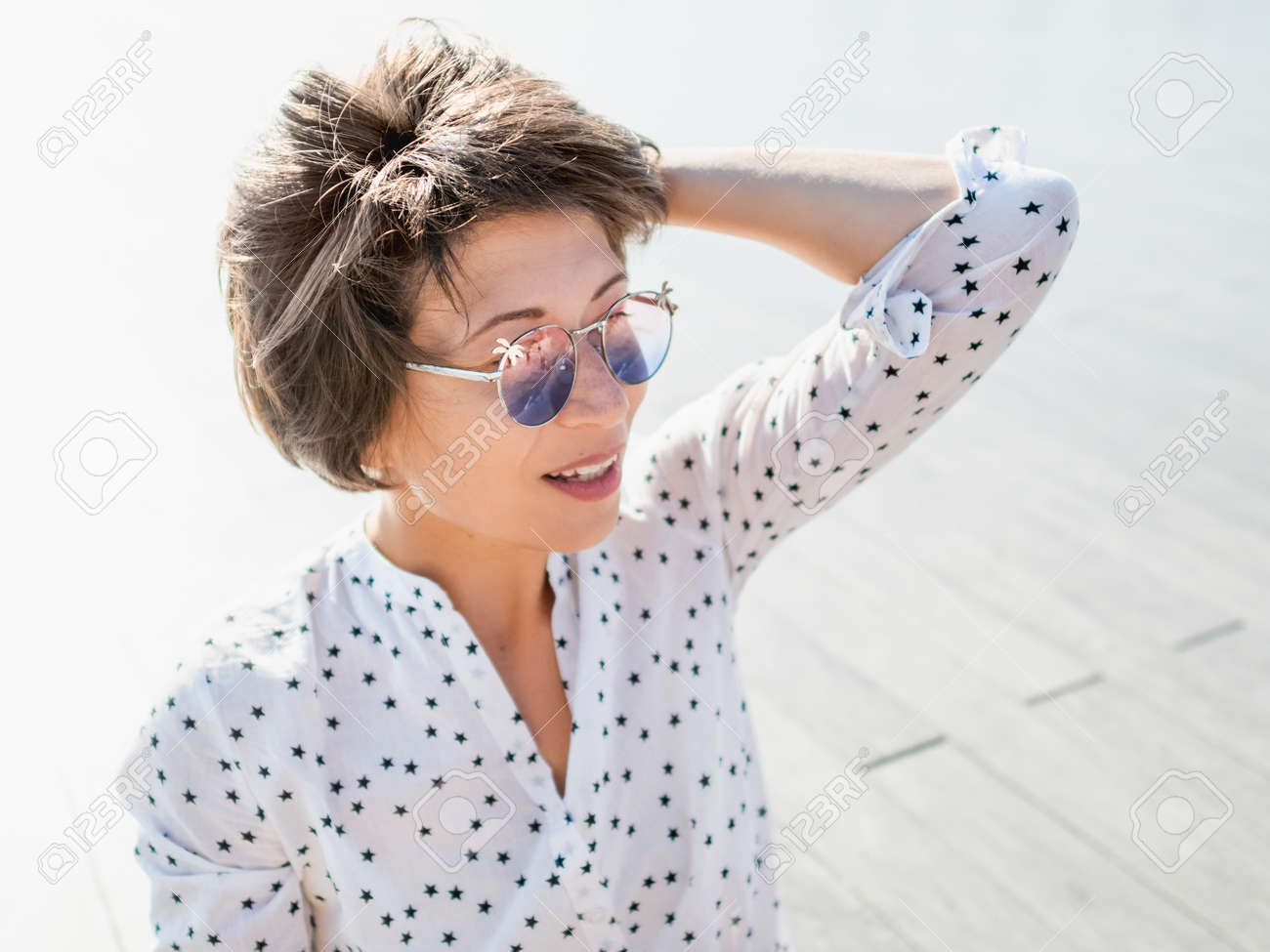 Wind ruffles short hair of freckled woman in colorful sunglasses. Smiling woman at open wooden scene of urban park. Summer vibes. Sincere emotions. - 172806628