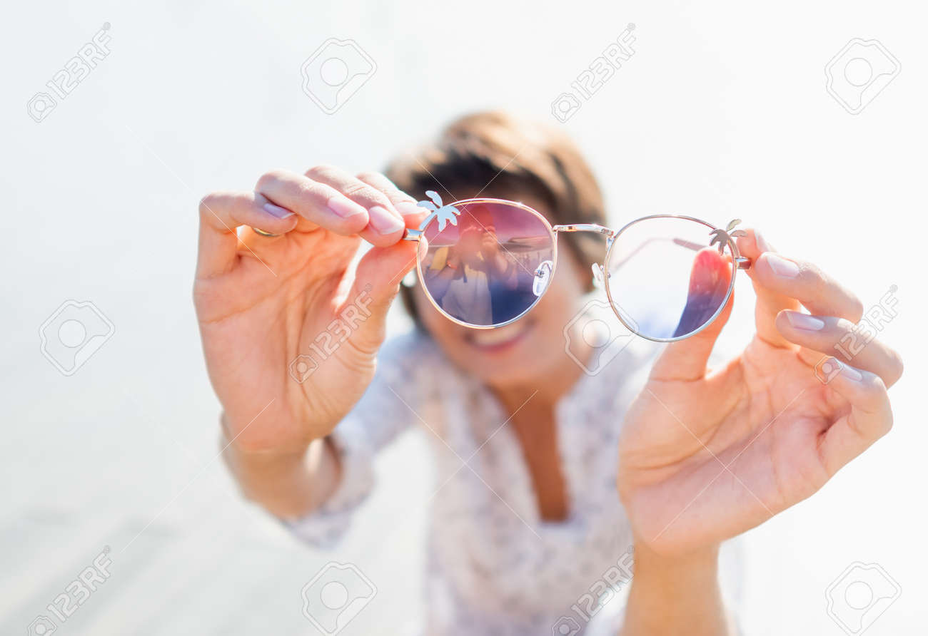 Woman with short hair looks through colorful sunglasses. Smiling woman at open wooden scene of urban park. Summer vibes. Sincere emotions. - 172806635