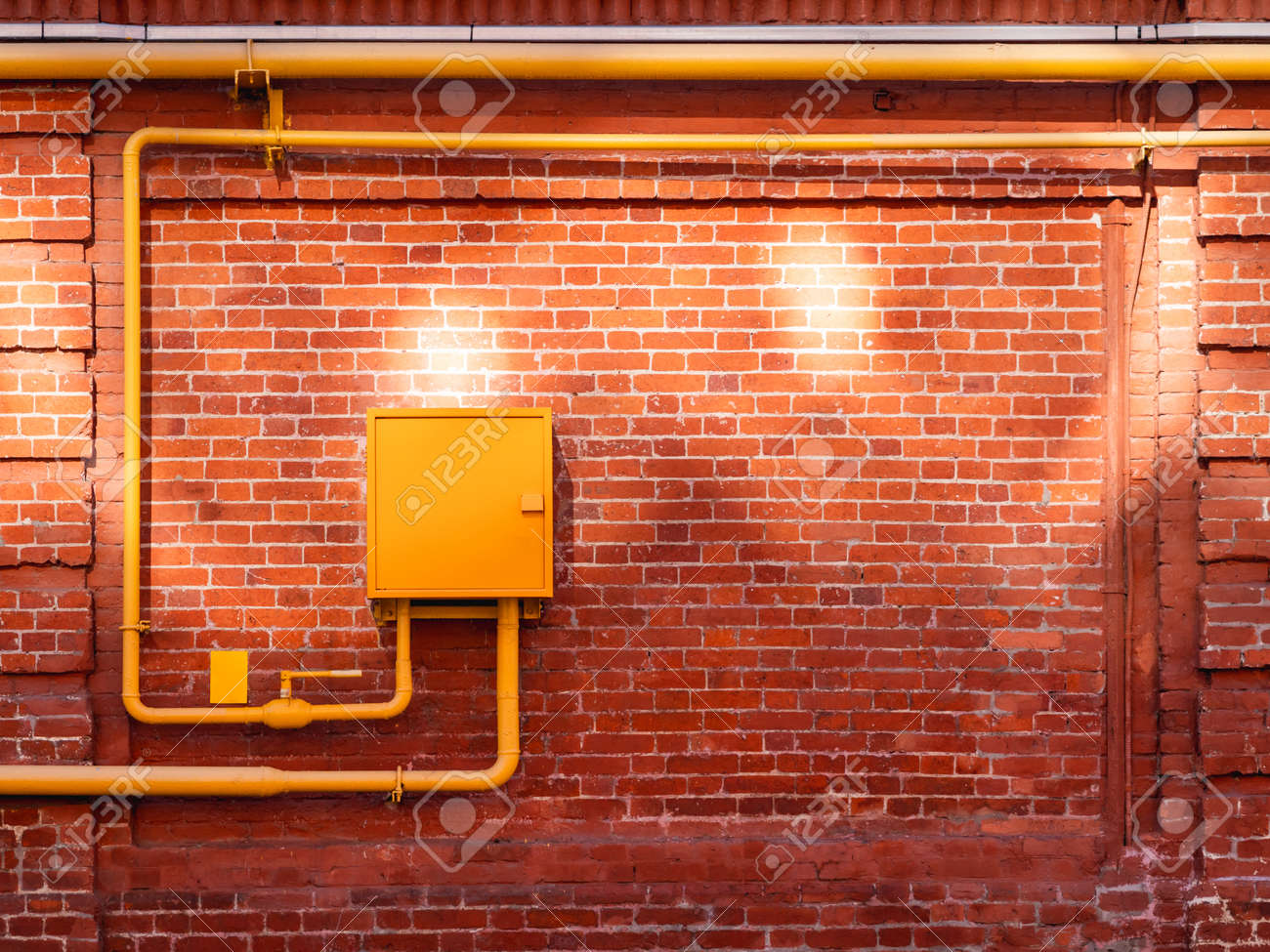 Red brick wall with yellow gas pipes and sunbeams. Old wall with sun reflections. Old building with shabby surface. - 172806603