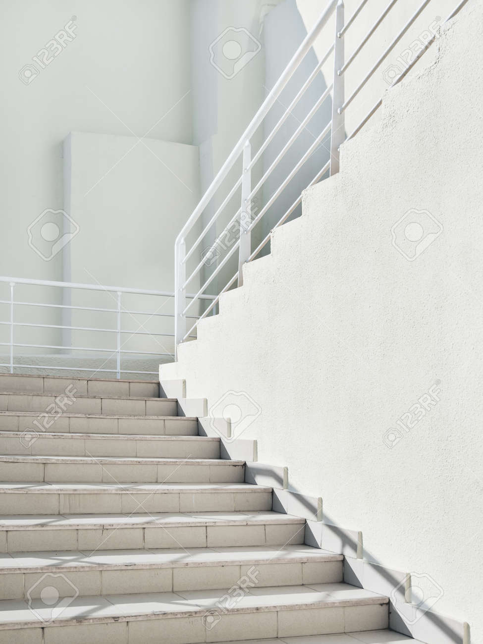 White exterior of outdoor staircase with railing. Sunlight and shadow on stone steps. Urban geometry. - 172806611