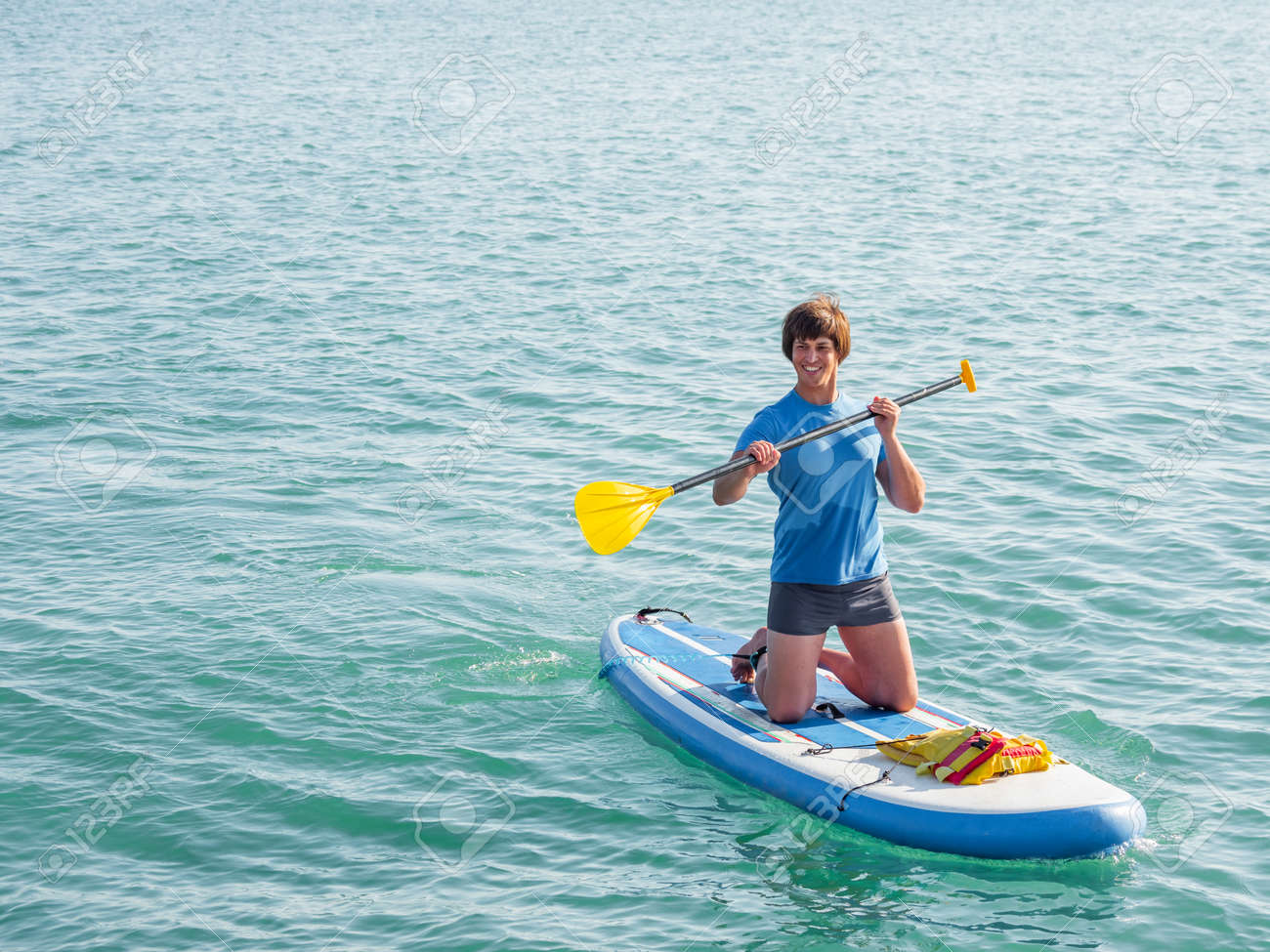 Paddle boarder. Sportsman on knees paddling on stand up paddleboard. SUP surfing. Active lifestyle. Outdoor recreation. Vacation on seaside. - 172806594