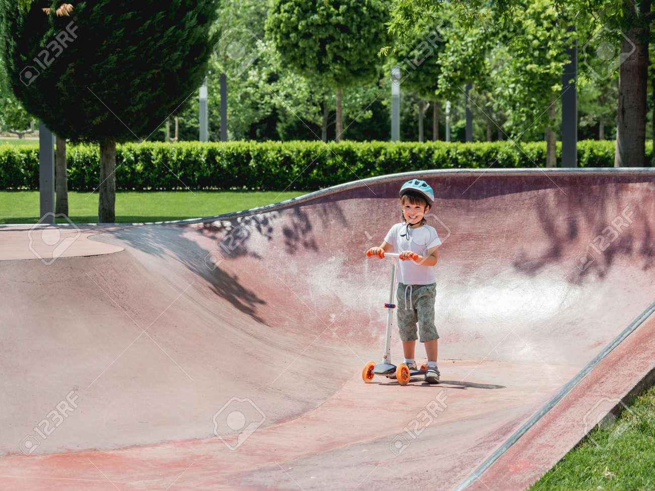 Little boy rides kick scooter in skate park. Special concrete bowl structures in urban park. Training to skate at summer. - 172806598
