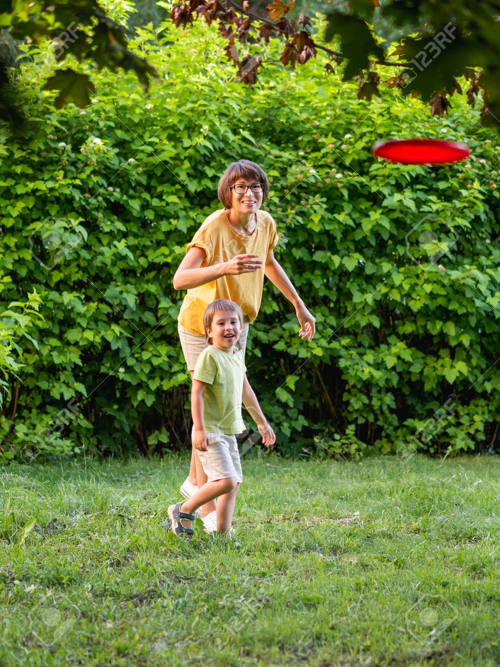 Mother and son play flying disk on grass lawn. Summer vibes. Outdoor leisure activity. Family life. Sports game at backyard. - 172806600