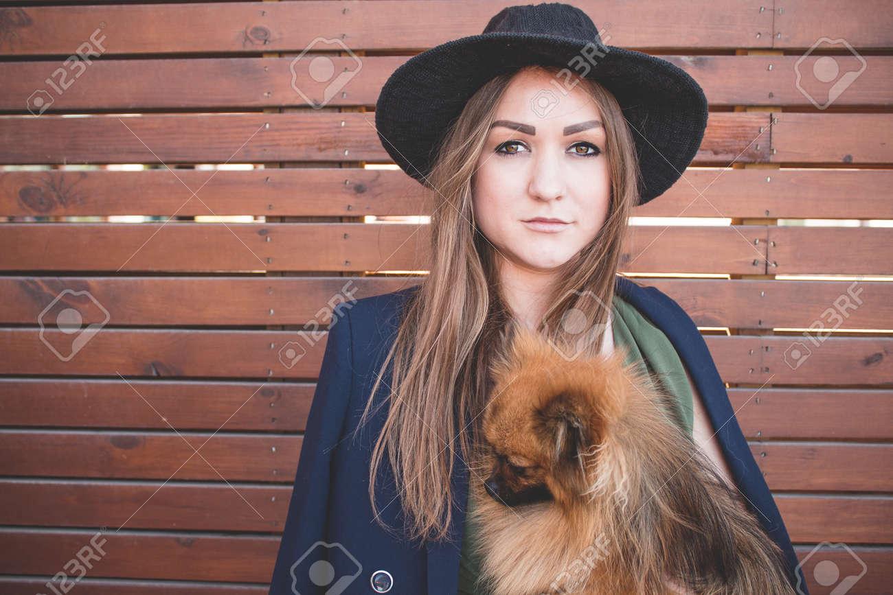 034b2b2fe0a0 Archivio Fotografico - Giovane bella ragazza in un cappello nero e vestito  lungo su una priorità bassa di legno marrone con il piccolo cane