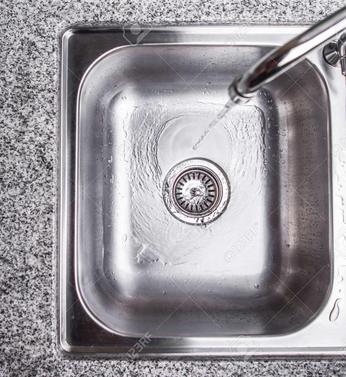 Banque dimages leau qui coule dans le trou dans un évier de cuisine