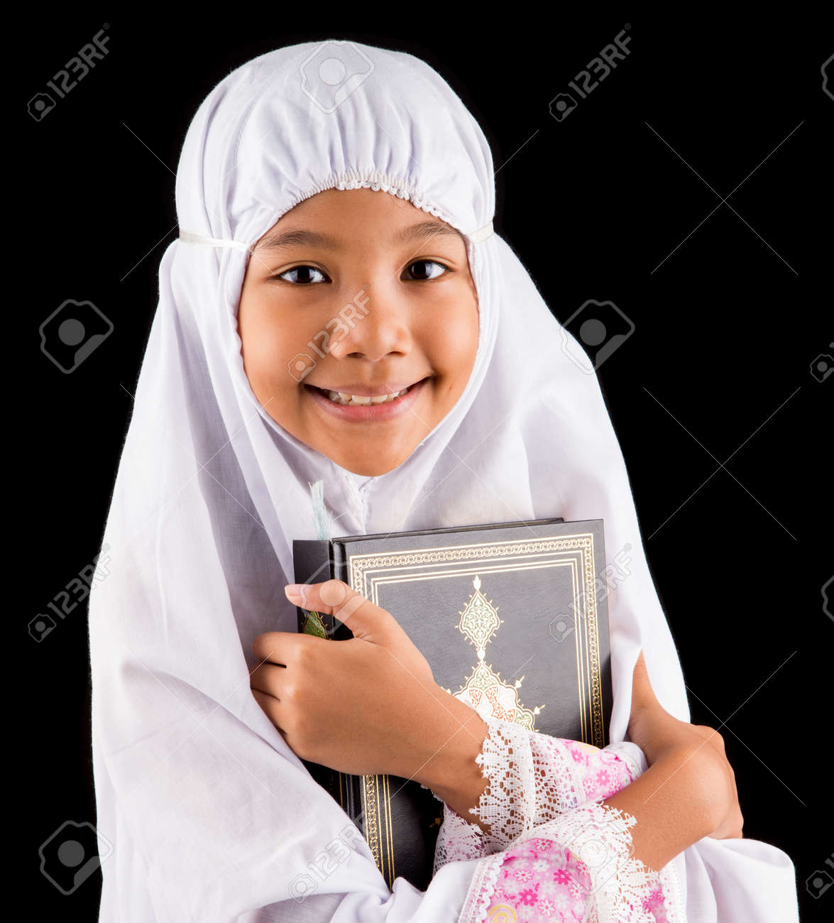 young asian muslim girl in white hijab with al quran over black
