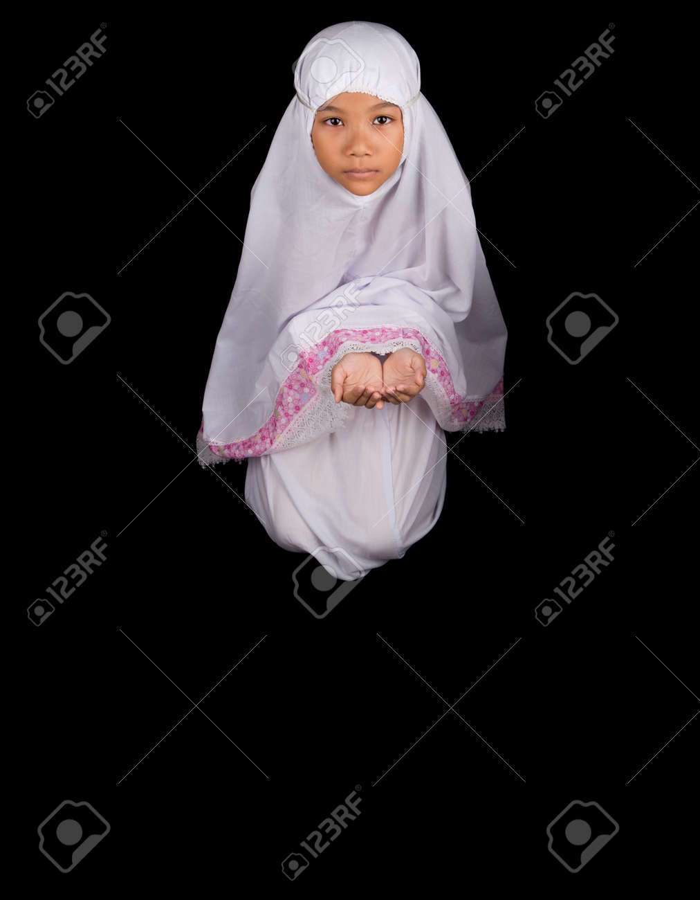 Stock photo young asian muslim girl in white hijab cupped her hands saying a prayer over black background