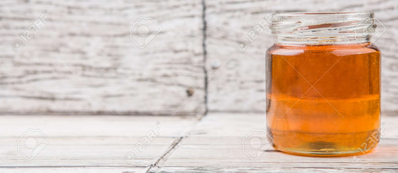 Honey In A Mason Jar Over Rustic Weathered Wooden Background Stock Photo