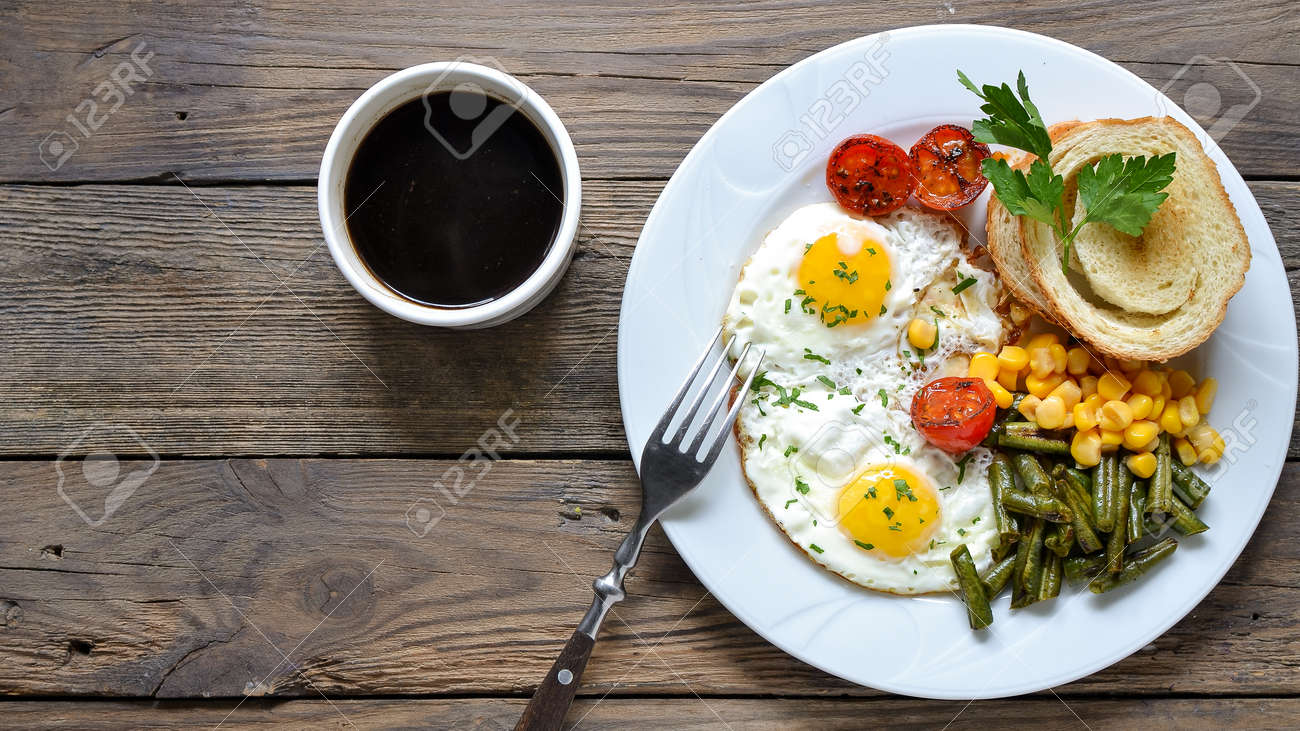 Fried eggs with tomatoes, green beans, corn and toast. English vegetarian breakfast. Top view. Coffee and fried eggs on a wooden tray. Wood background - 148172652