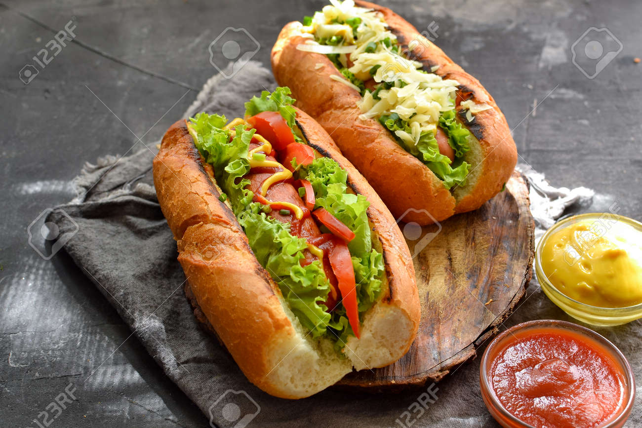 Hot dogs with various fillings. Dark background. food background with copy space. Hot dogs with mustard and ketchup, lettuce, cheese and tomatoes. - 156150687