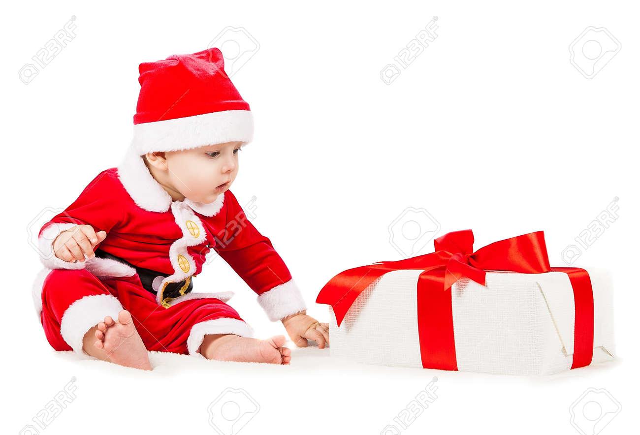 Archivio Fotografico - Gioiosa piccolo bambino vestito da Babbo Natale con  un grande regalo di Natale in una scatola 5699f115f53