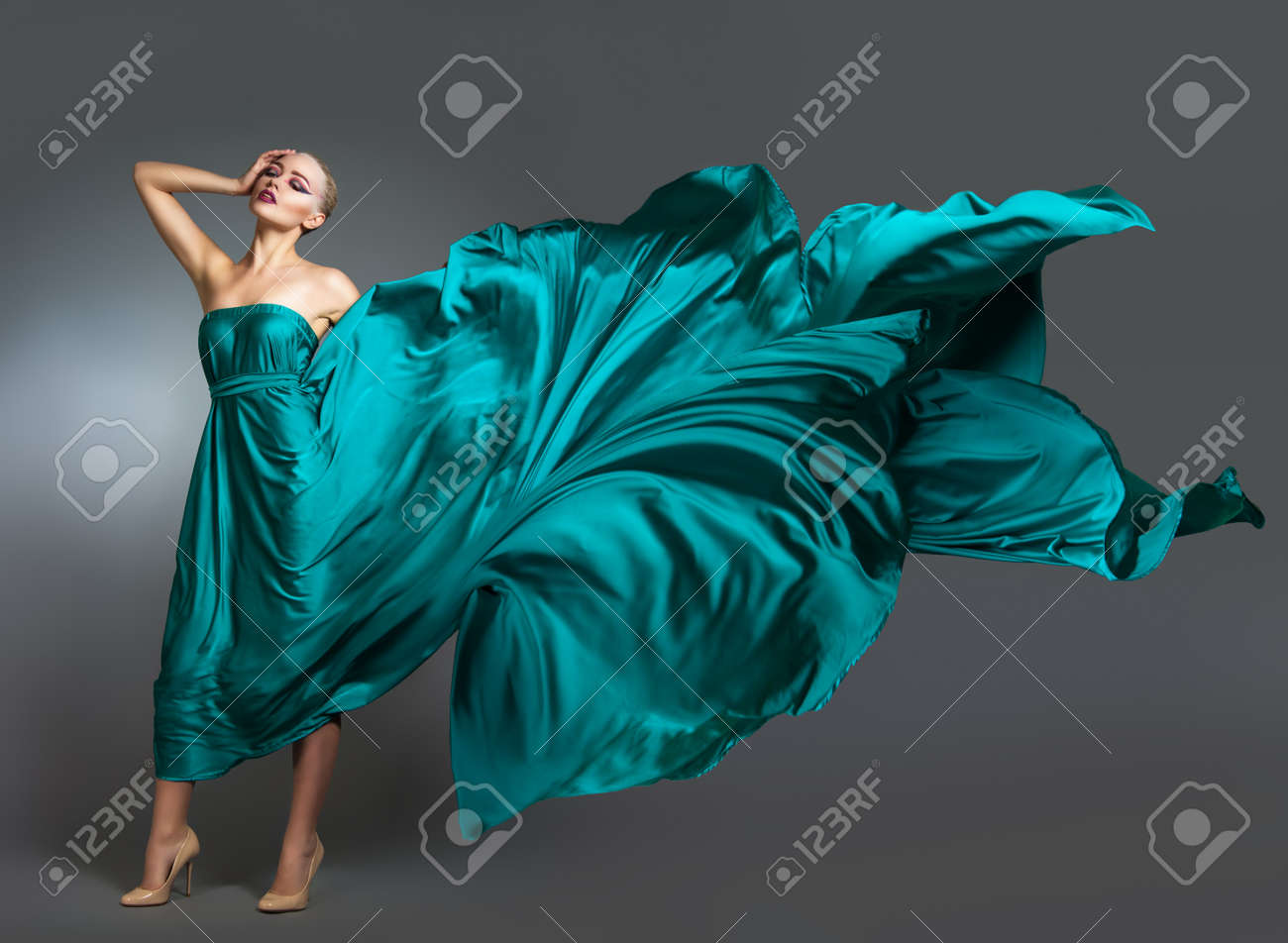 Woman in silk dress waving on wind. Flying and fluttering gown cloth over gray background Woman Dancing In Fashion Dress - 51333997