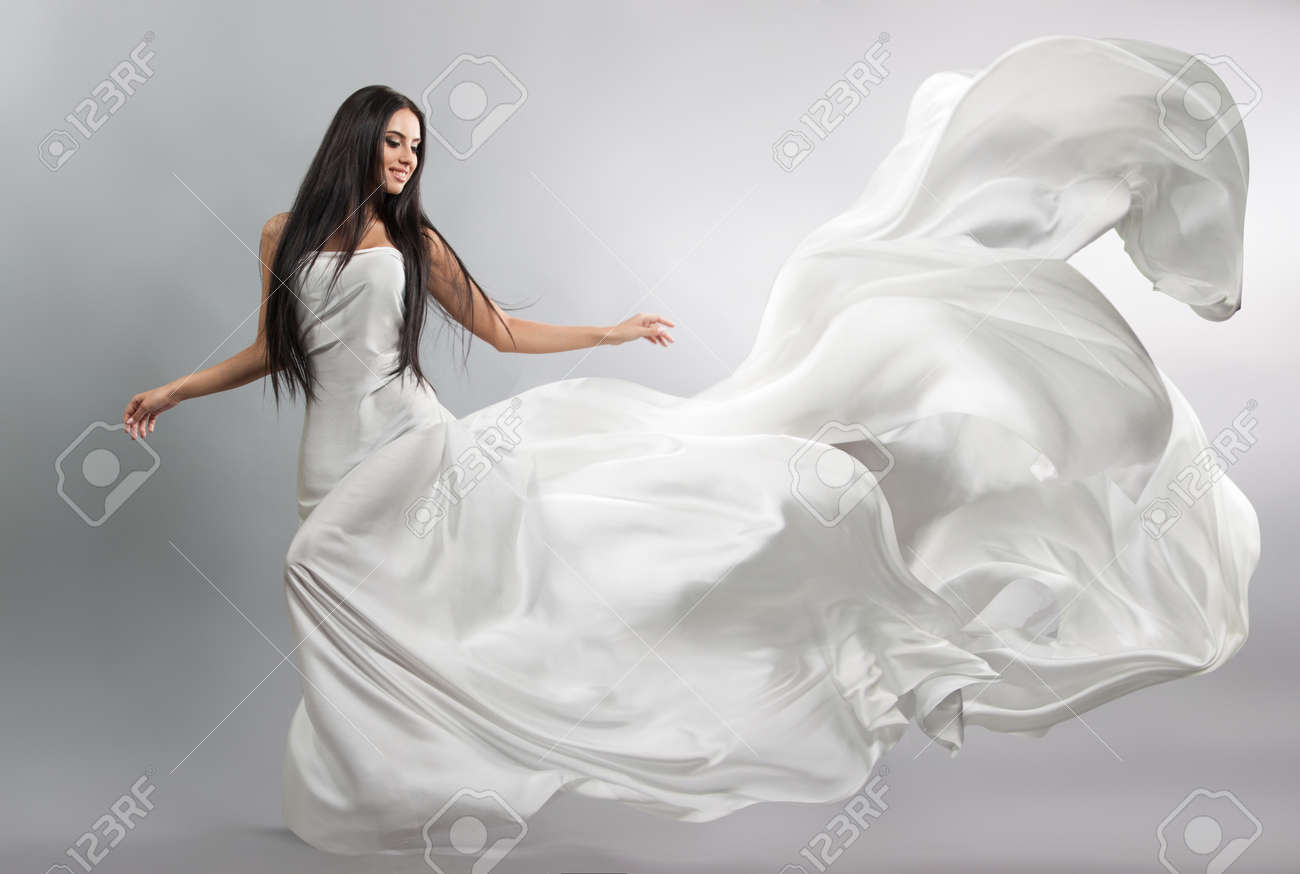 beautiful young girl in flying white dress. Flowing fabric. Light white cloth flying in the wind - 62374955