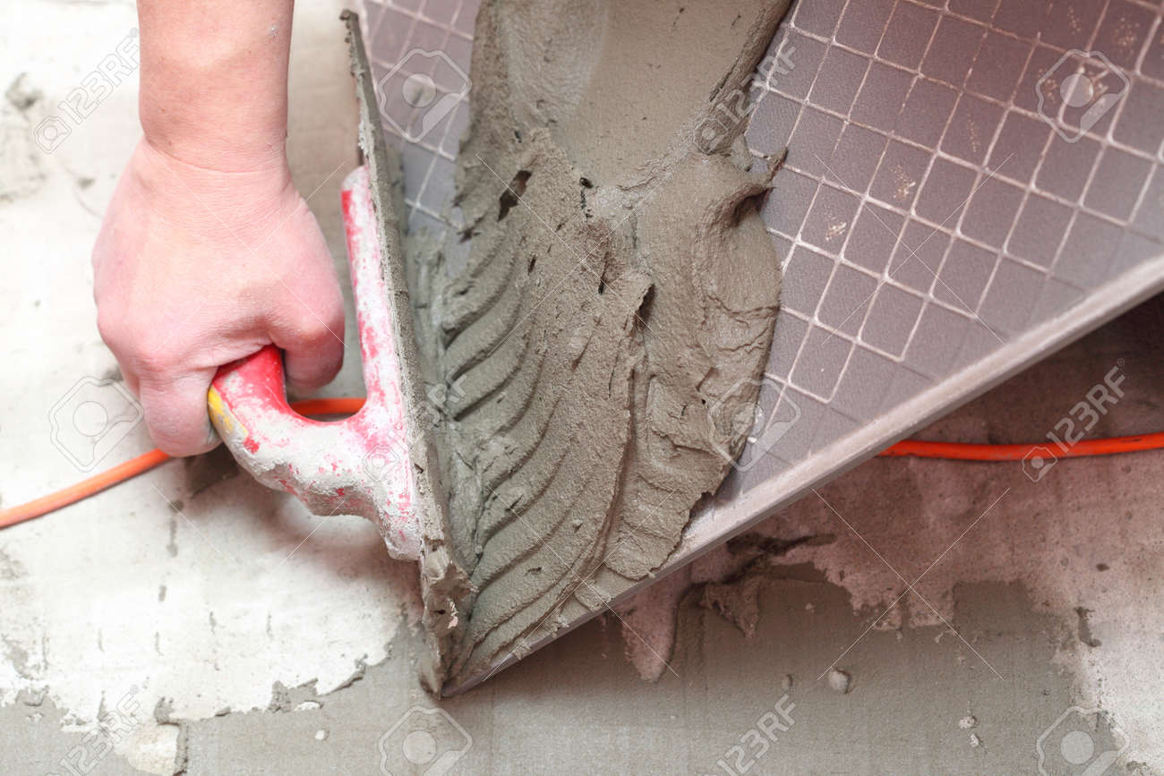 Man Construction worker is tiling at home, tile floor adhesive Stock Photo - 15848924