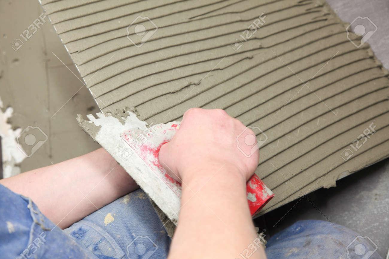 Operaio edile è piastrelle in casa colla per piastrelle pavimento