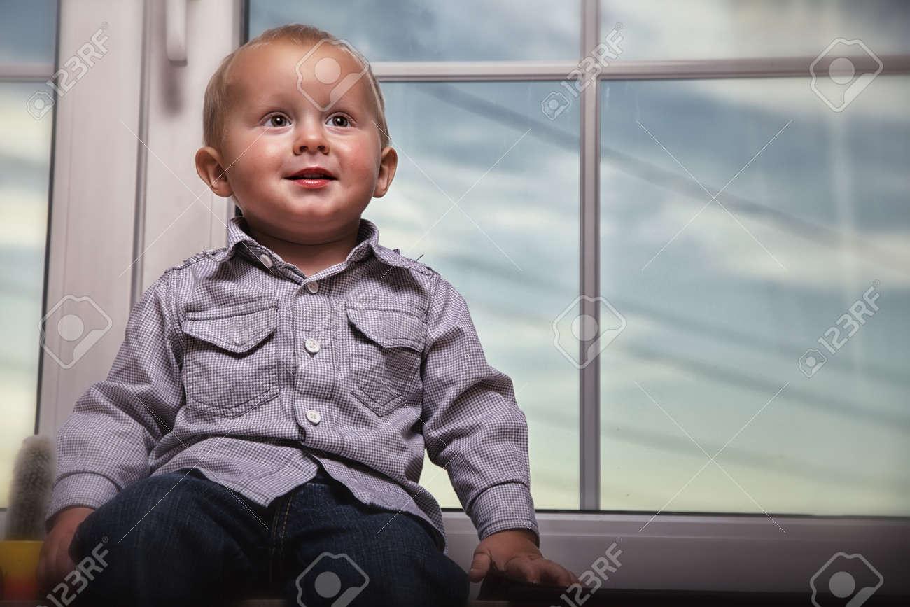 little boy sitting on window Stock Photo - 17481444
