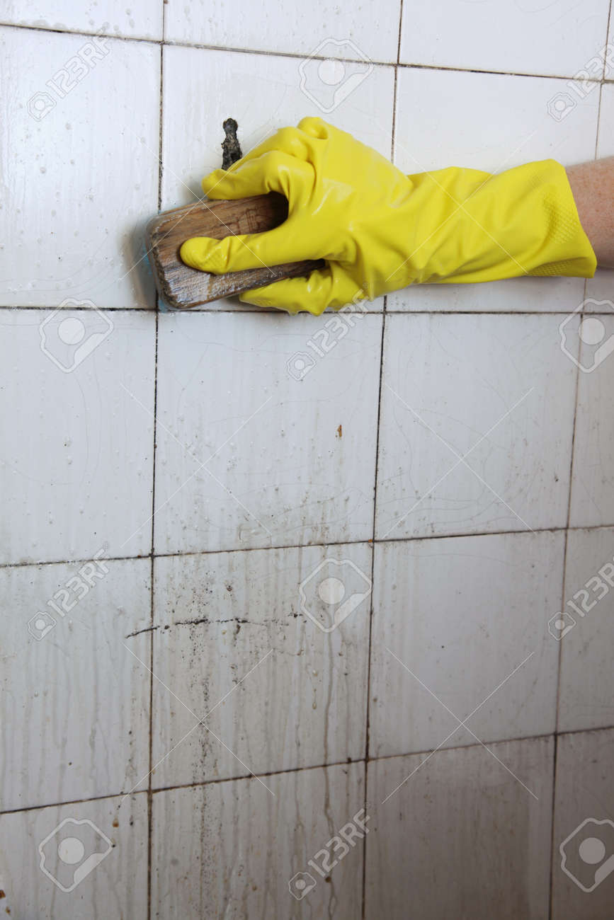 gloved hand cleaning dirty old tiles with brush in a bathroom Stock Photo    17873724. Gloved Hand Cleaning Dirty Old Tiles With Brush In A Bathroom