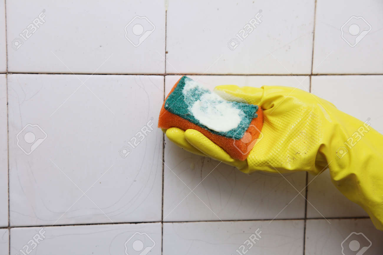 Gloved Hand Cleaning Dirty Old Tiles With Sponge In A Bathroom Stock ...