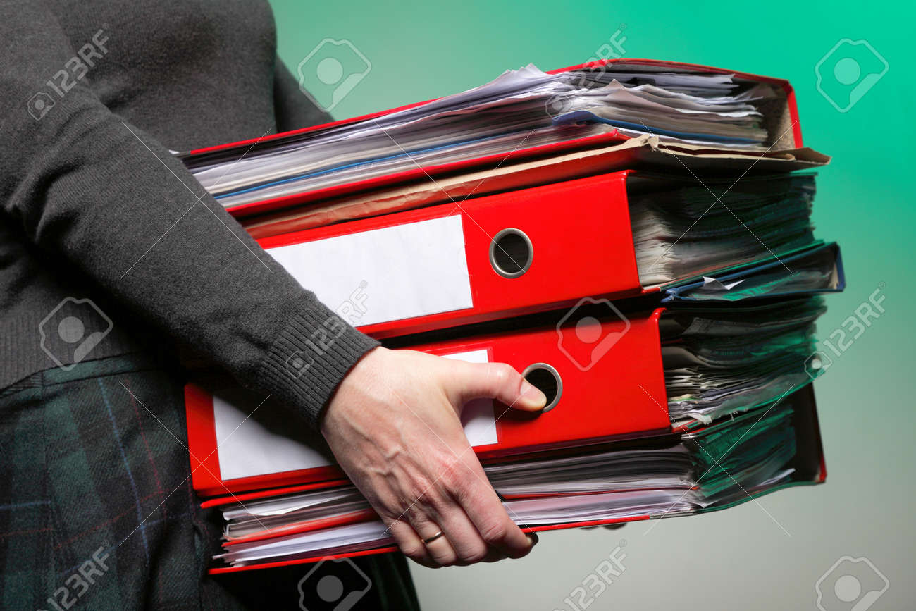 woman in grey holding stack of folders. Pile with old documents and bills on green background Stock Photo - 17874843