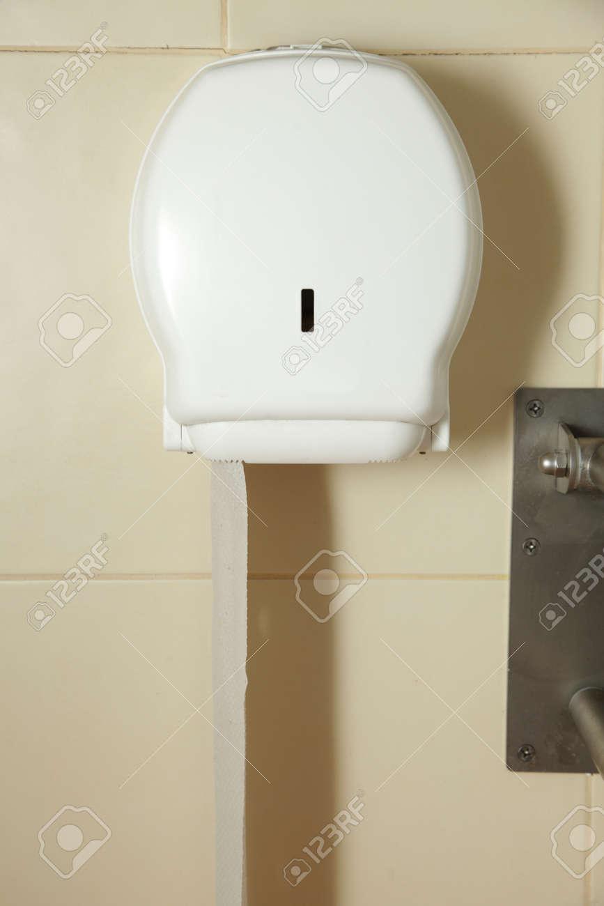 Papier hygiénique accroché au mur. Le papier de toilette dans la boîte de  carrelage beige
