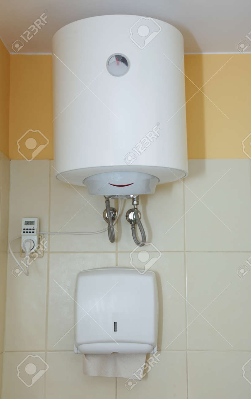 Paper towel dispenser and electric water heater on the wall in the bathroom  Stock Photo. Paper Towel Dispenser And Electric Water Heater On The Wall In