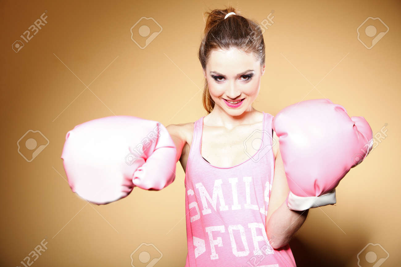 Female boxer model wearing big fun pink gloves playing sports boxing studio shot, brown background Stock Photo - 20327592
