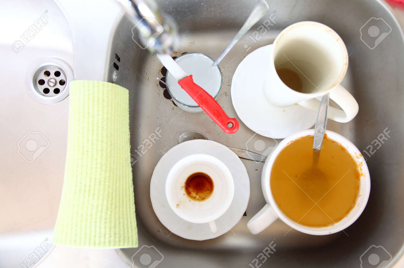 Kitchen Sink With Dishes washing up. white dirty dishes in the kitchen sink. stock photo
