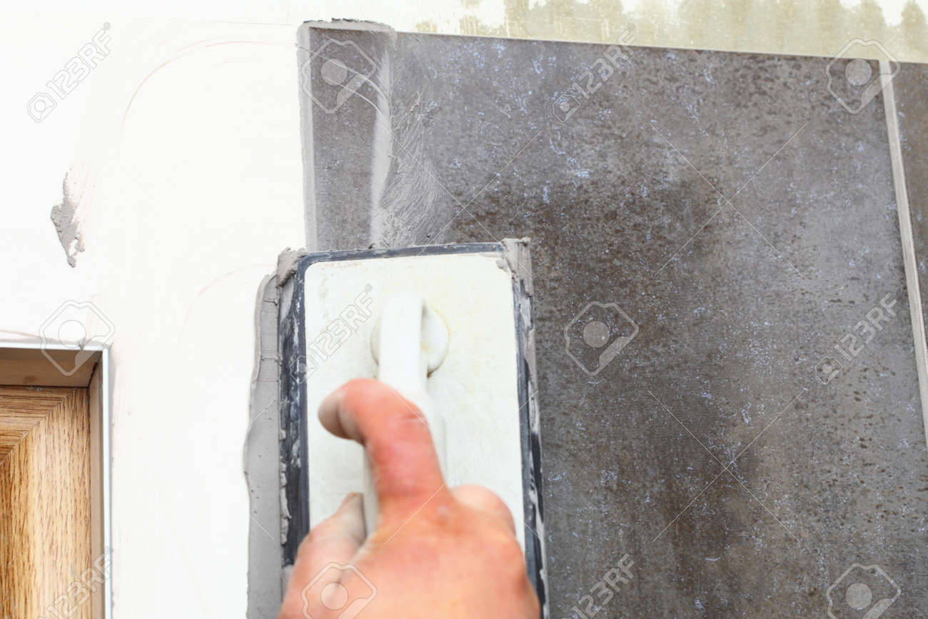 Home improvement, renovation - construction worker tiler is tiling, ceramic tile floor adhesive, trowel with mortar Stock Photo - 23568470