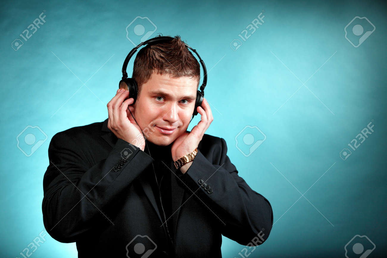 Young Happy Man Student With Headphones Listening To Music Blue