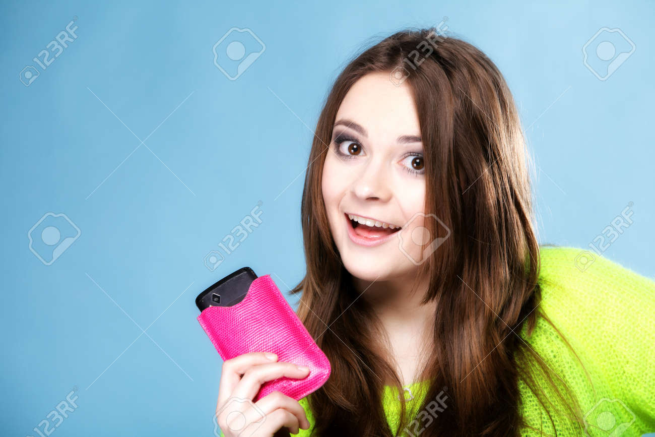 Happy girl young woman with mobile phone smartphone in pink cover studio shot blue background Stock Photo - 24254860