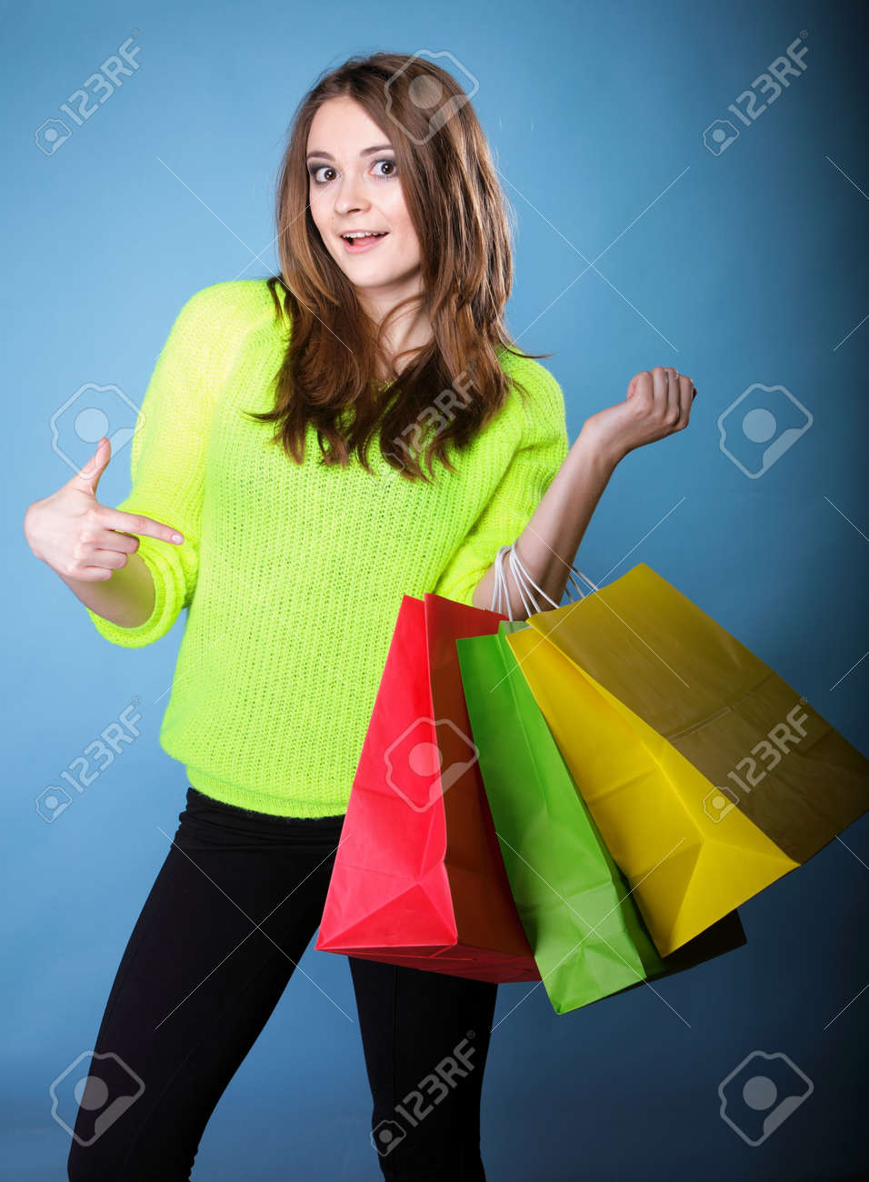 young woman in bright vivid colour sweater with paper multi coloured shopping bags on blue background. Sales and discounts concept. Stock Photo - 24254891