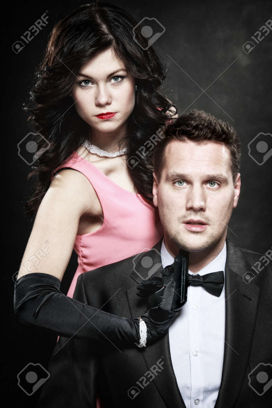 Detective theme. Retro style attractive couple, rich gangster and charming woman sexy detective spy with gun on black background Stock Photo - 24255196
