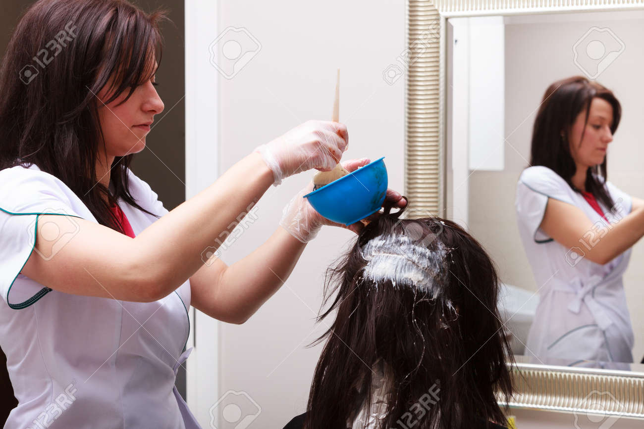 Professional female hairdresser applying color to female customer at design hair salon, woman having her hair dyed, Hair dye colouring in process - 24908943