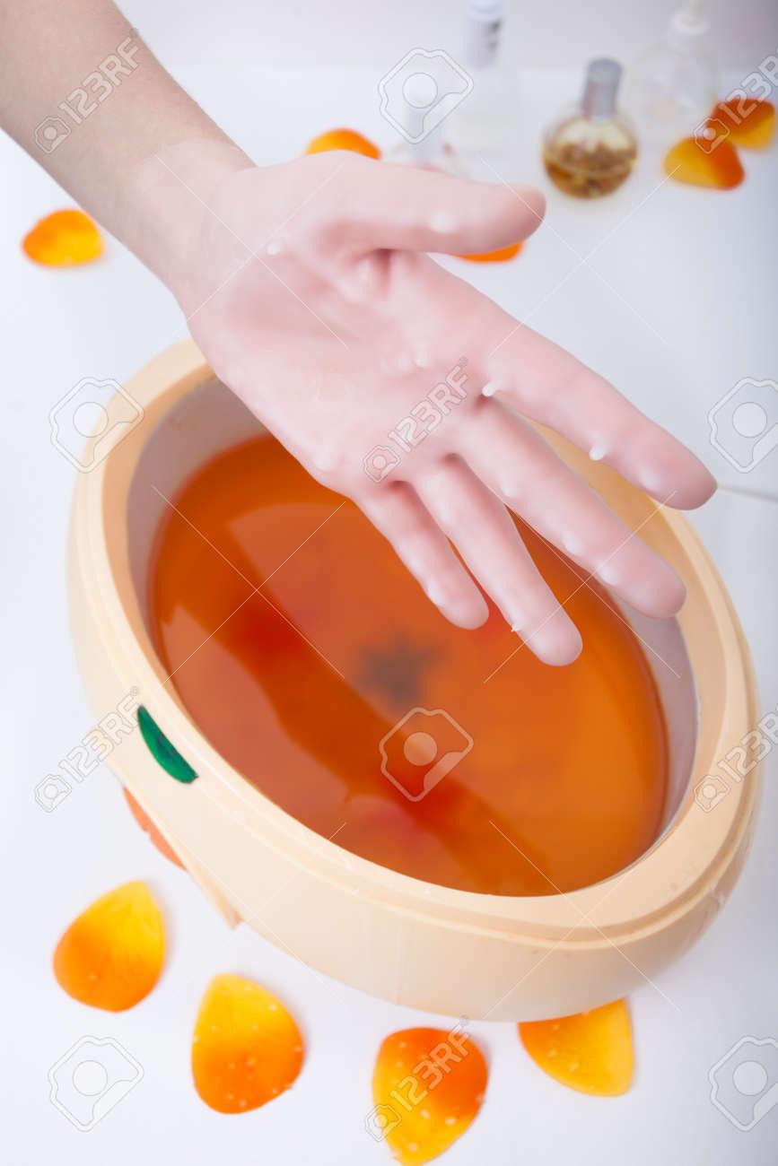 Weibliche Hand Und Orange Paraffin-Wachs In Der Schüssel Maniküre ...
