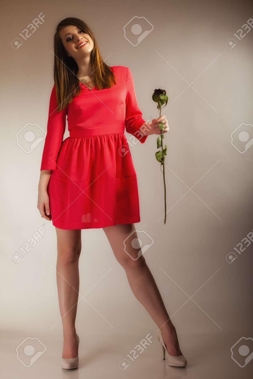 44ff32aa83 Foto de archivo - Mujer hermosa de la manera en la niña llena longitud  adolescente en vestido rojo con rosa secos sobre fondo gris