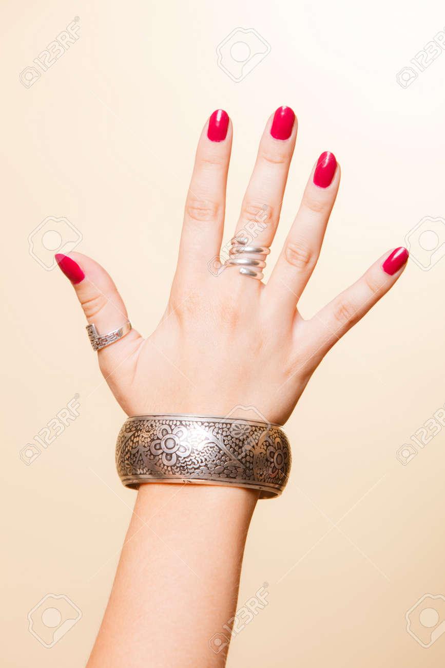 クローズ アップ女性の手、女性示すファッショナブルなアクセサリー宝石でアームレットと指のリング。赤の美しさは爪します。