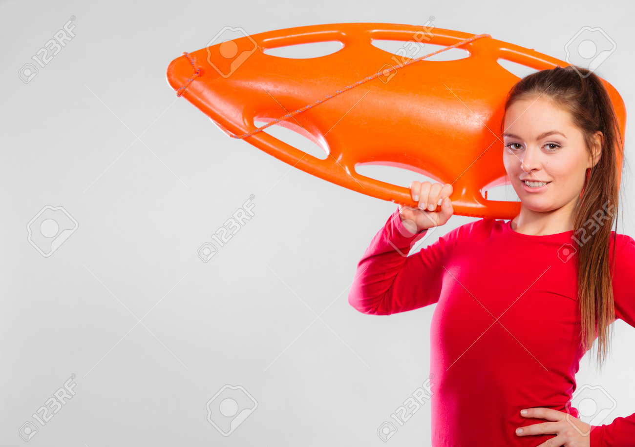 469f145a261 Accident prevention and water rescue. Young woman female lifeguard on duty  holding float lifesaver equipment