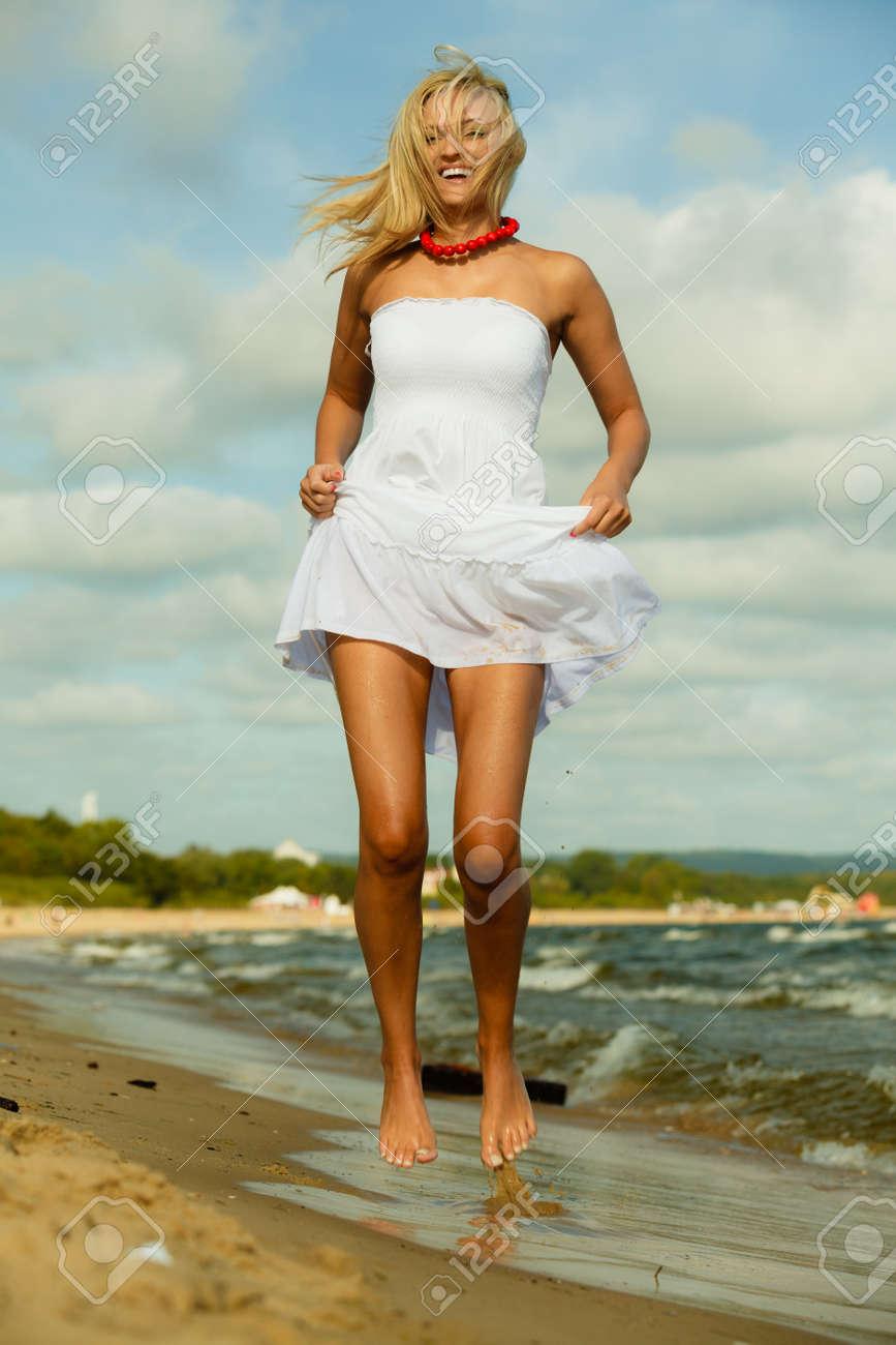 34554e2f6f36 Bella ragazza in abito bianco che salta sulla spiaggia. Giovane donna  divertirsi a rilassarsi sulla costa del mare.