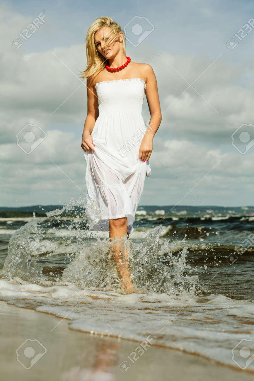 e15873c2989d Bella ragazza in abito bianco in esecuzione sulla spiaggia. Giovane donna  divertirsi relax sulla costa del mare.