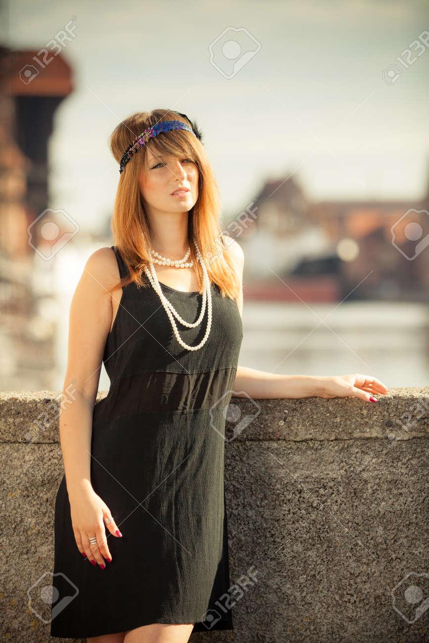 Rétro style de la mode femme vintage rugissant années 1920 en plein air sur  la rue. La vieille ville de Gdansk Dantzig en arrière,plan