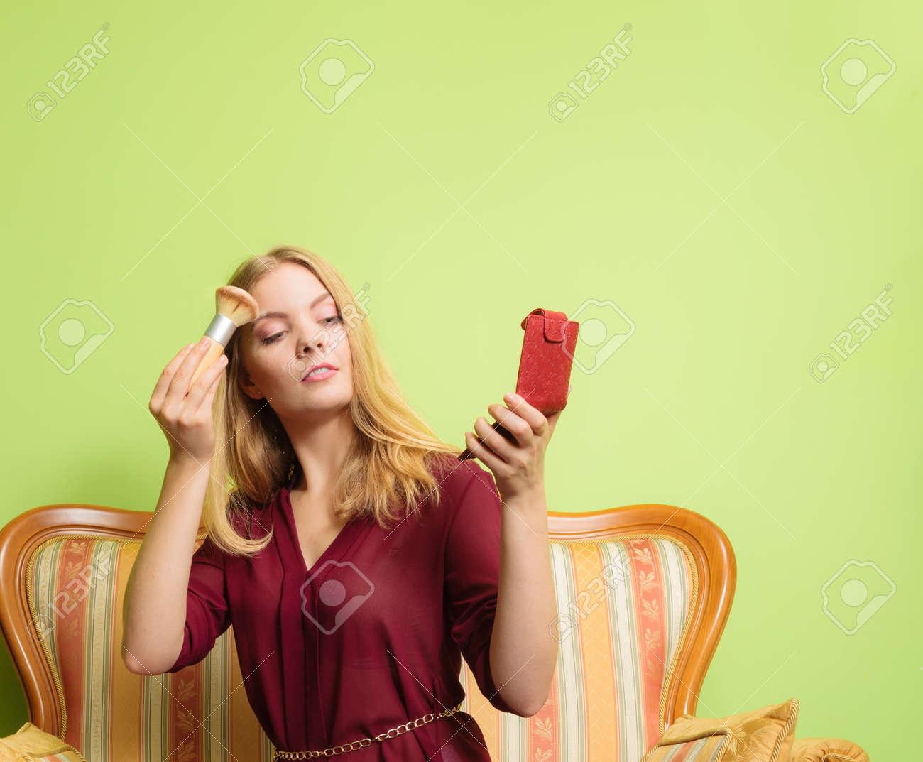 72792114c Foto de archivo - Mujer atractiva joven aplicar maquillaje con pincel de  polvo. Bastante hermosa niña sentada en el sofá sofá retro vintage.