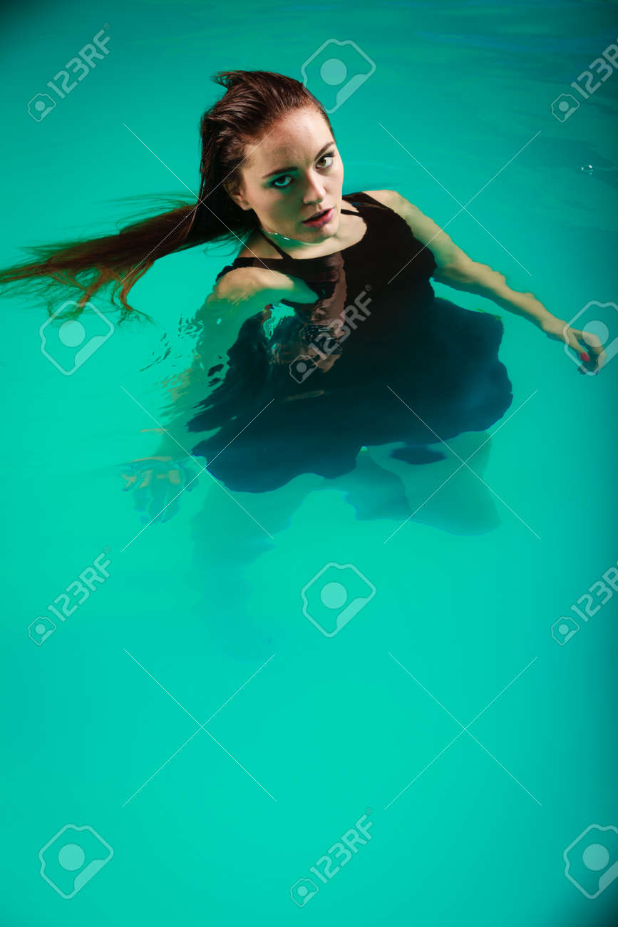 Sexy Seductive Woman Wearing Black Dress In Swimming Pool Water