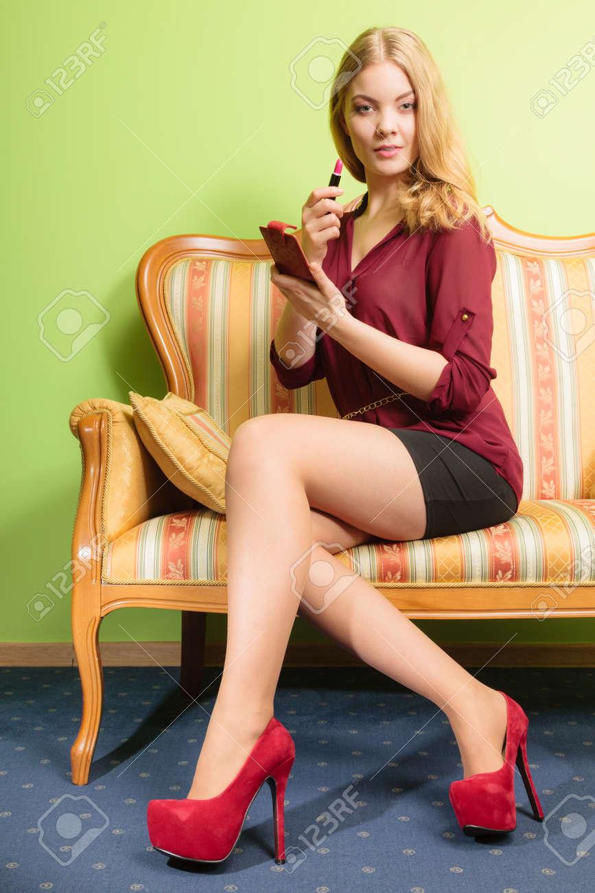 6a24e4cc2 Foto de archivo - Mujer atractiva joven que aplicar el lápiz labial en los  labios. Bastante hermosa niña sentada en el sofá sofá retro vintage.