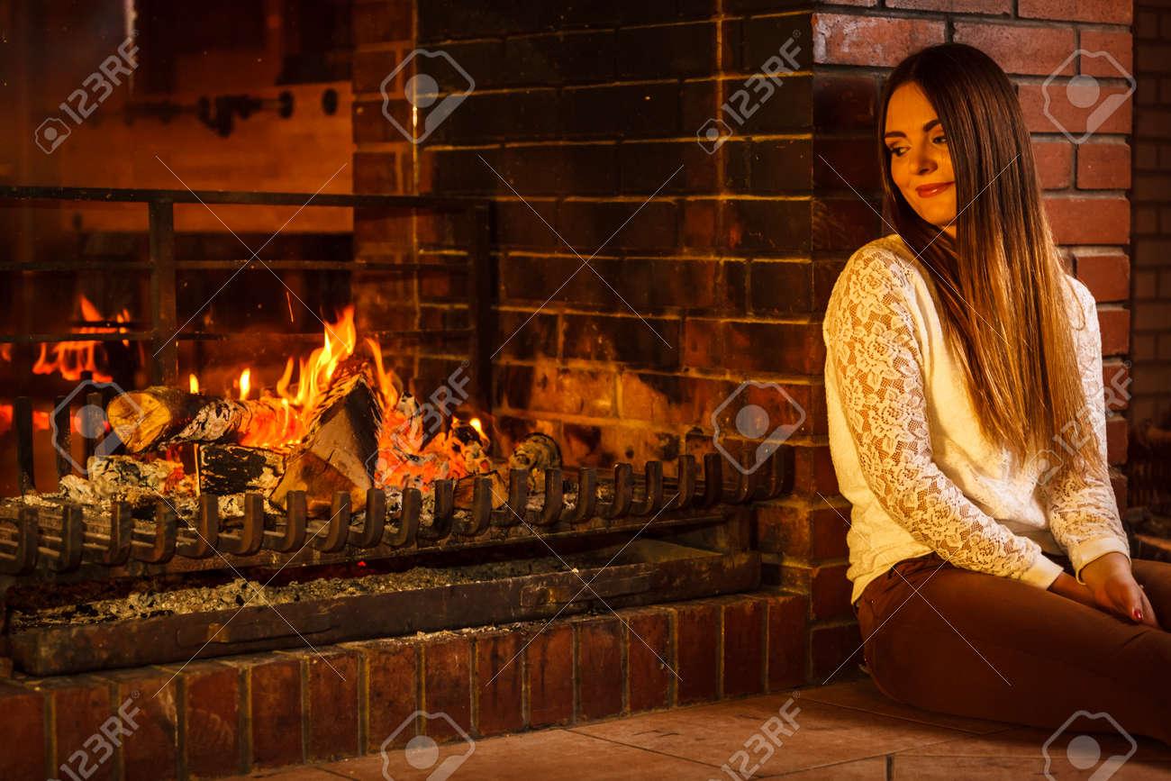 melancholic pensive woman relaxing resting at fireplace