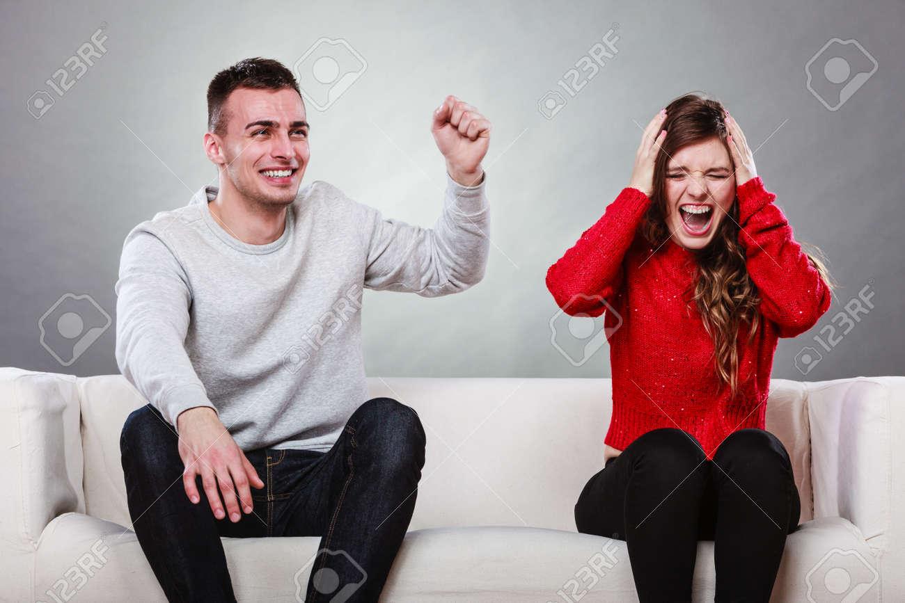 Furious Angry Upset Woman And Happy Joyful Husband Sitting On